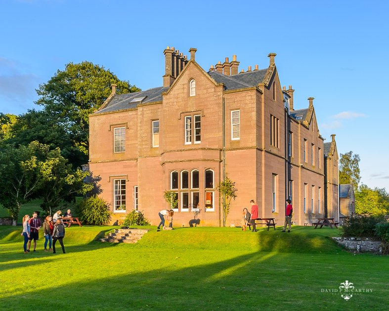 Students relaxing in the grounds of a large country house in Scotland